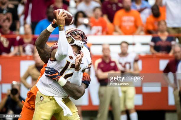 Chris Slayton of the Syracuse Orange hits Deondre Francois of the Florida State Seminoles as he passes the ball during the first quarter at the...