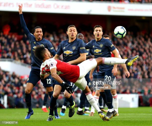 Chris Smalling Nemanja Matic and Diogo Dalot of Manchester United watch on as PierreEmerick Aubameyang of Arsenal acrobatically shoots on goal during...