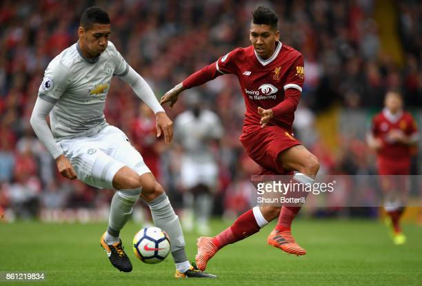 Chris Smalling of Manchester United and Roberto Firmino of Liverpool battle for possession during the Premier League match between Liverpool and...