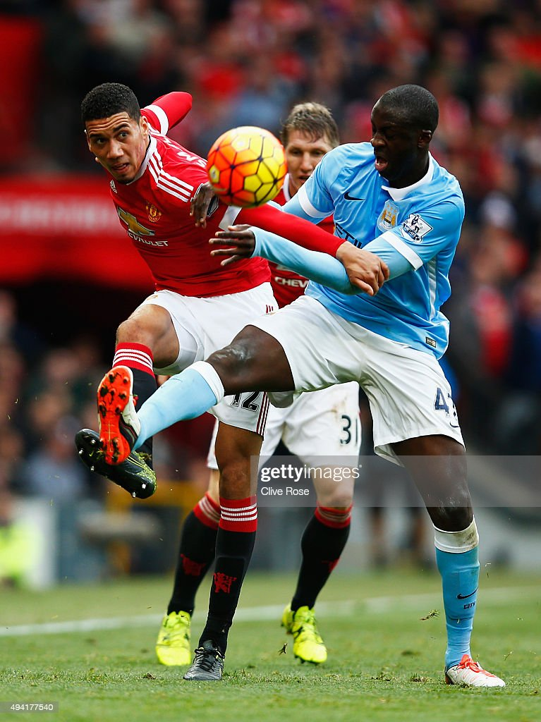 Chris Smalling of Manchester United and Yaya Toure of Manchester City compete for the ball during the Barclays Premier League match between Manchester United and Manchester City at Old Trafford on October 25, 2015 in Manchester, England.