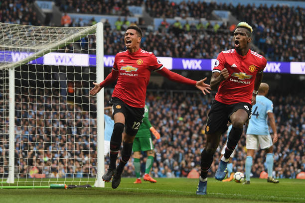 Chris Smalling of Manchester United celebrates scoring his side's third goal with Paul Pogba during the Premier League match between Manchester City...