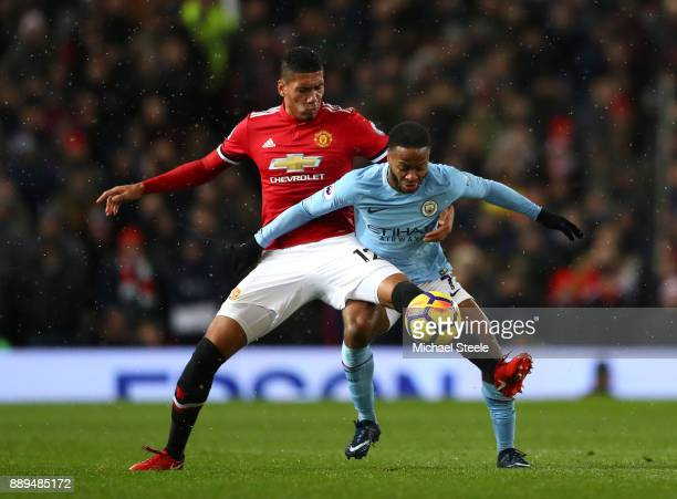 Chris Smalling of Manchester United holds off Raheem Sterling of Manchester City during the Premier League match between Manchester United and...