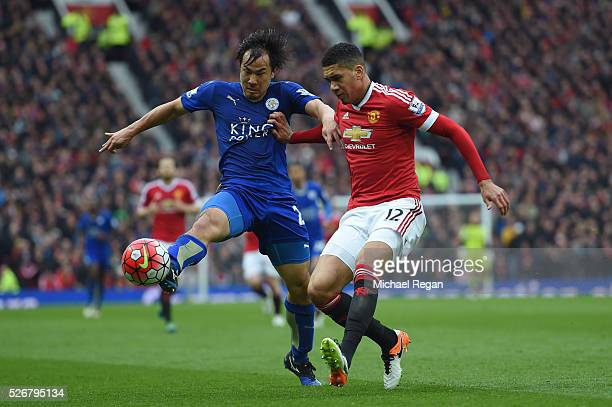 Chris Smalling of Manchester United is challenged by Shinji Okazaki of Leicester City during the Barclays Premier League match between Manchester...