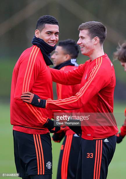 Chris Smalling of Manchester United jokes around with teammate Paddy McNair during a training session ahead of the UEFA Europa League round of 16...