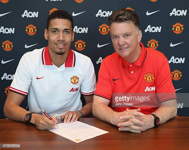 Chris Smalling of Manchester United poses with manager Louis van Gaal after signing a contract extension at Aon Training Complex on April 21 2015 in...