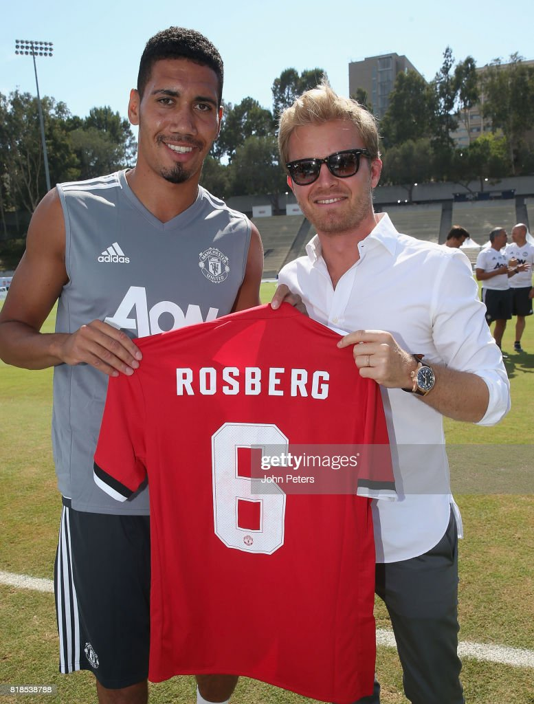 Chris Smalling of Manchester United presents Formula One world champion Nico Rosberg with a Unietd shirt ahead of a first team training session as part of their pre-season tour of the USA at UCLA on July 18, 2017 in Los Angeles, California.
