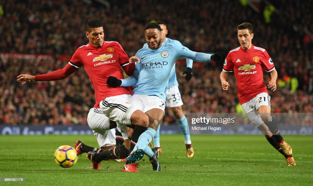 Chris Smalling of Manchester United tackles Raheem Sterling of Manchester City as Ander Herrera of Manchester United looks on during the Premier League match between Manchester United and Manchester City at Old Trafford on December 10, 2017 in Manchester, England.