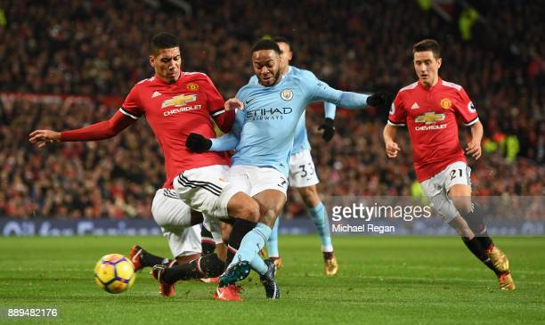 Chris Smalling of Manchester United tackles Raheem Sterling of Manchester City as Ander Herrera of Manchester United looks on during the Premier...