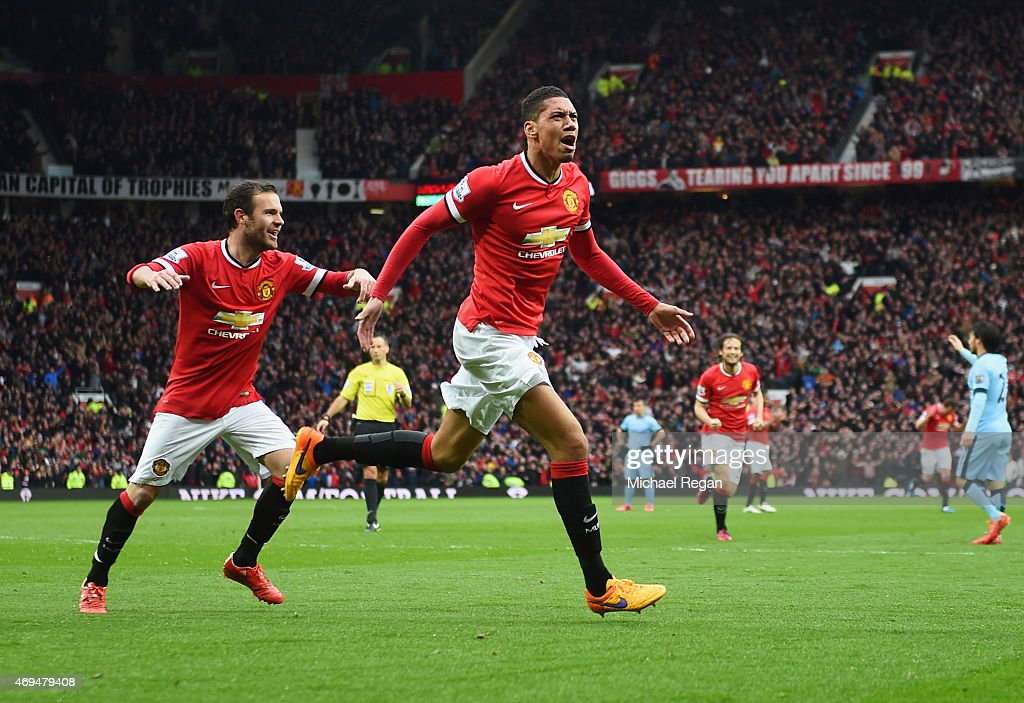 Chris Smalling of Manchester United with celebrates with Juan Mataas he scores their fourth goal during the Barclays Premier League match between Manchester United and Manchester City at Old Trafford on April 12, 2015 in Manchester, England.