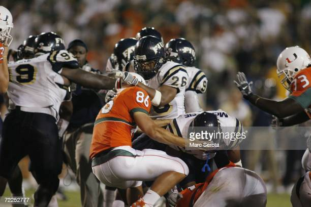 Chris Smith and Marshall McDuffie Jr #24 of the Florida International Panthers fight Ross Abramson of the Miami Hurricanes during an on field fight...
