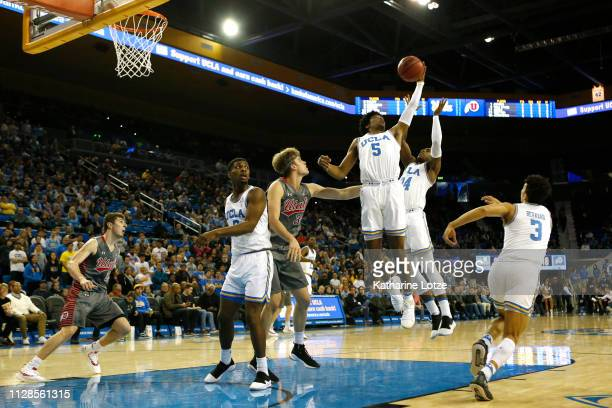 Chris Smith of the UCLA Bruins and Jalen Hill of the UCLA Bruins reach to grab a rebound during the first half of a game against the Utah Utes at...