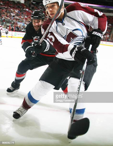 Chris Stewart of the Colorado Avalanche struggles with Niclas Wallin of the Carolina Hurricanes during an NHL game on January 8 2010 at RBC Center in...