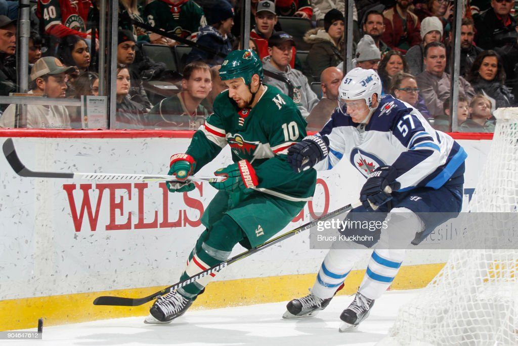 Chris Stewart #10 of the Minnesota Wild and Tyler Myers #57 of the Winnipeg Jets skate to the puck during the game at the Xcel Energy Center on January 13, 2018 in St. Paul, Minnesota.