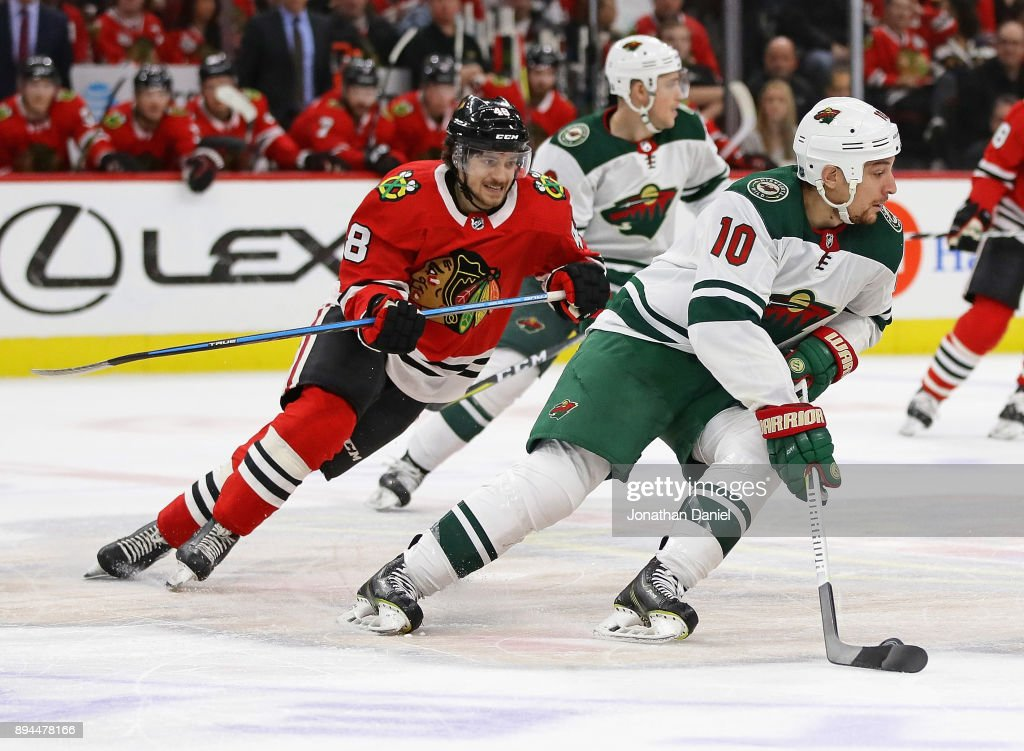 Chris Stewart #10 of the Minnesota Wild turns with the puck in front of Vinnie Hinostroza #48 of the Chicago Blackhawks at the United Center on December 17, 2017 in Chicago, Illinois. The Blackhawks defeated the Wild 4-1.