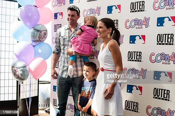 Chris Stewart of the New York Yankees poses with his family prior to the preview of the CCandy line during the CCandy Fashion Show at the MLB Fan...