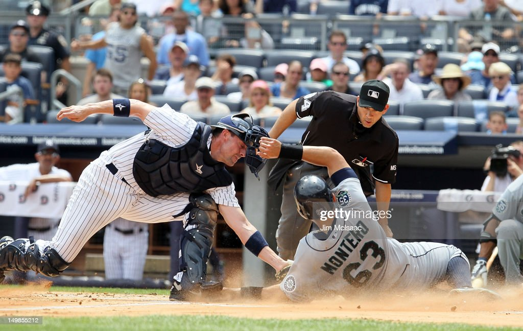 Chris Stewart #19 of the New York Yankees tags out Jesus Montero #63 of the Seattle Mariners to end the first inning at Yankee Stadium on August 5, 2012 in the Bronx borough of New York City.