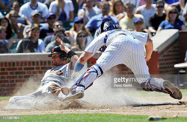 Chris Stewart of the San Francisco Giants scores as Koyie Hill ofthe Chicago Cubs makes a late tag in the fifth inning during the first game of a...
