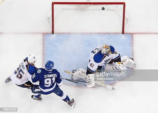 Chris Stewart of the St Louis Blues and Steven Stamkos of the Tampa Bay Lightning watch the puck go by goalie Jaroslav Halak of the St Louis Blues...