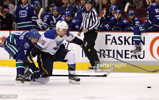 Chris Stewart of the St Louis Blues fights for the puck against Dan Hamhuis of the Vancouver Canucks during the first period of their NHL game at...