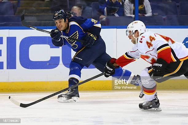 Chris Stewart of the St Louis Blues takes a shot on goal against Chris Butler of the Calgary Flames at the Scottrade Center on November 7 2013 in St...