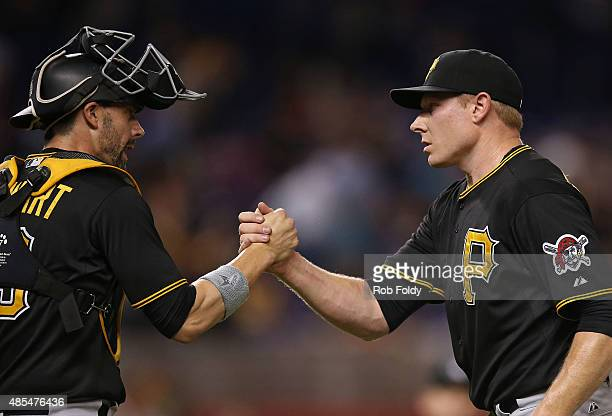 Chris Stewart shakes hands with Mark Melancon of the Pittsburgh Pirates after defeating the Miami Marlins in the game at Marlins Park on August 27...