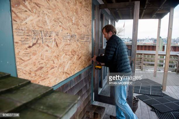 Chris Stoddard owner of Lucky Finn Cafe boards up the cafe before a storm known as a 'bomb cyclone' makes it way to the East Coast on March 1 2018 in...