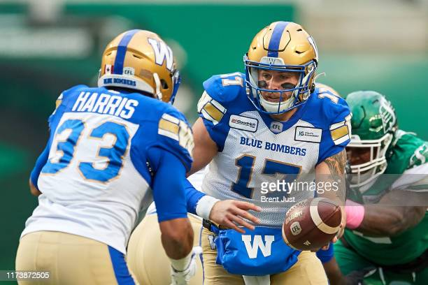 Chris Streveler hands the ball to Andrew Harris of the Winnipeg Blue Bombers in the first half of the game between the Winnipeg Blue Bombers and...