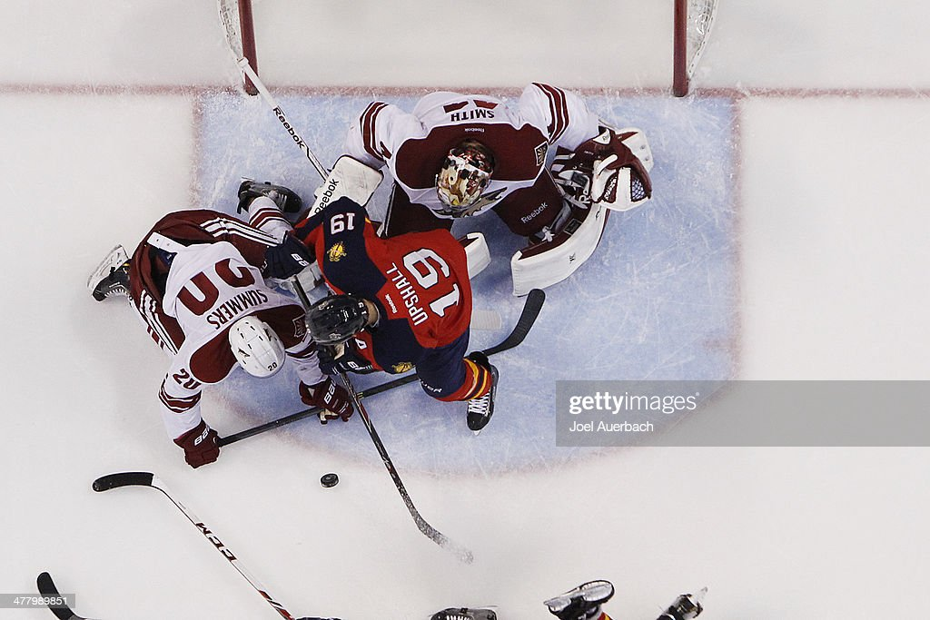 Chris Summers #20 assists goaltender Mike Smith #41 of the Phoenix Coyotes defend the net against the shot by Scottie Upshall #19 of the Florida Panthers at the BB&T Center on March 11, 2014 in Sunrise, Florida. The Coyotes defeated the Panthers 3-1.