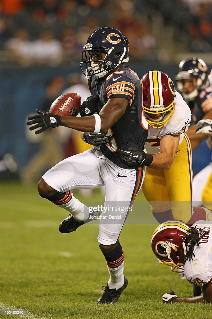 Chris Summers #83 of the Chicago Bears fumbles the ball as he is hit by Reed Doughty #37 of the Washington Redskins during a preseason game at Soldier Field on August 18, 2012 in Chicago, Illinois. The Bears defeated the Redskins 33-31.