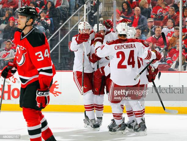 Chris Summers of the Phoenix Coyotes is congratulated by his teammates after scoring a second period goal as Jon Merrill of the New Jersey Devils...