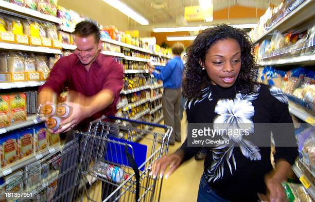 DENVER COLO NOVEMBER 1 2005 Chris Tanaka<cq> left and Josina Anderson<cq> of Fox Sports<cq> race to load their shopping cart with $15503 of...