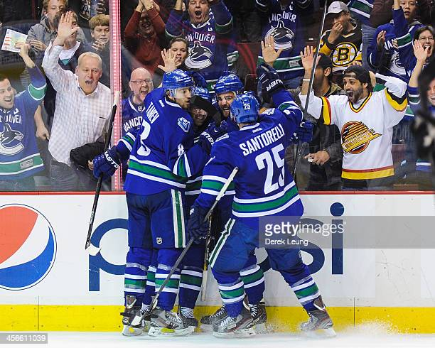 Chris Tanev, Dan Hamhuis, and Chris Higgins and Mike Santorelli of the Vancouver Canucks celebrate after Chris Higgins scored the team's third goal...