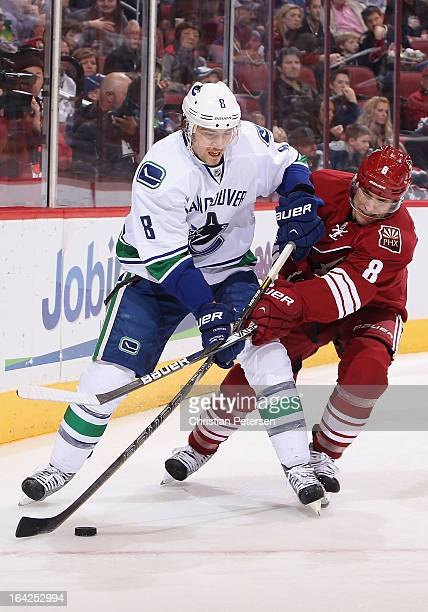 Chris Tanev of the Vancouver Canucks handles the puck under pressure from Matthew Lombardi of the Phoenix Coyotes during the first period of the NHL...