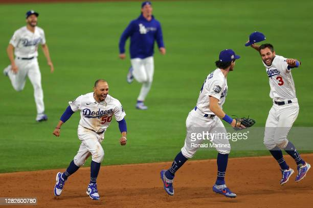 Chris Taylor, Cody Bellinger and Mookie Betts of the Los Angeles Dodgers celebrate after defeating the Tampa Bay Rays 3-1 in Game Six to win the 2020...