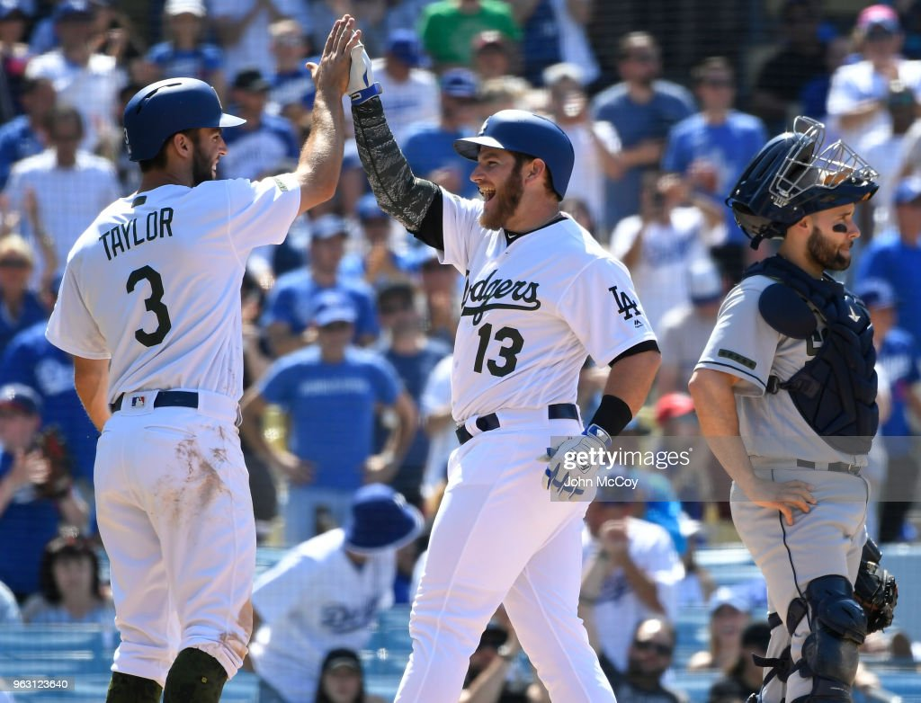 Chris Taylor #3 of the Los Angeles Dodgers congratulates Max Muncy #13 on his two-run home run in the eighth inning while Raffy Lopez #0 of the San Diego Padres stands at the plate at Dodger Stadium on May 27, 2018 in Los Angeles, California.
