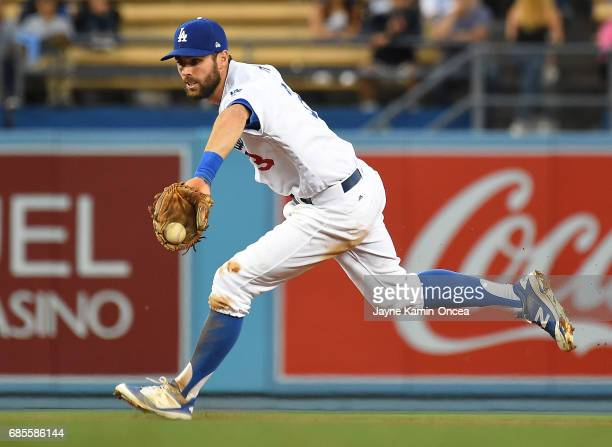 Chris Taylor of the Los Angeles Dodgers fields the ball hit by Christian Colon of the Miami Marlins and flips it to Corey Seager of the Los Angeles...