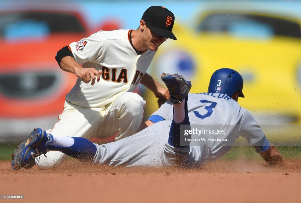 Chris Taylor #3 of the Los Angeles Dodgers gets caught stealing tagged out at second base by Kelby Tomlinson #37 of the San Francisco Giants in the top of the eighth inning at AT&T Park on April 8, 2018 in San Francisco, California.