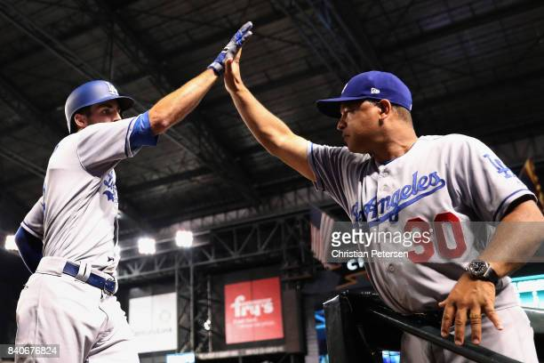 Chris Taylor of the Los Angeles Dodgers high fives manager Dave Roberts after hititng a two run home run against the Arizona Diamondbacks during the...