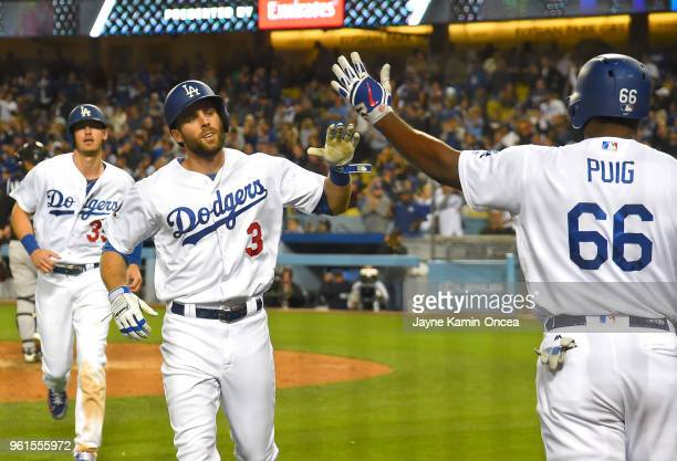 Chris Taylor of the Los Angeles Dodgers is greeted by Yasiel Puig as he heads to the dugout after hitting a tworun home run scoring Cody Bellinger in...