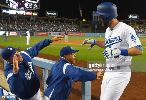 Chris Taylor of the Los Angeles Dodgers is greeted in the dugout by bench coach Bob Geren and manager Dave Roberts after hitting a tworun home in the...