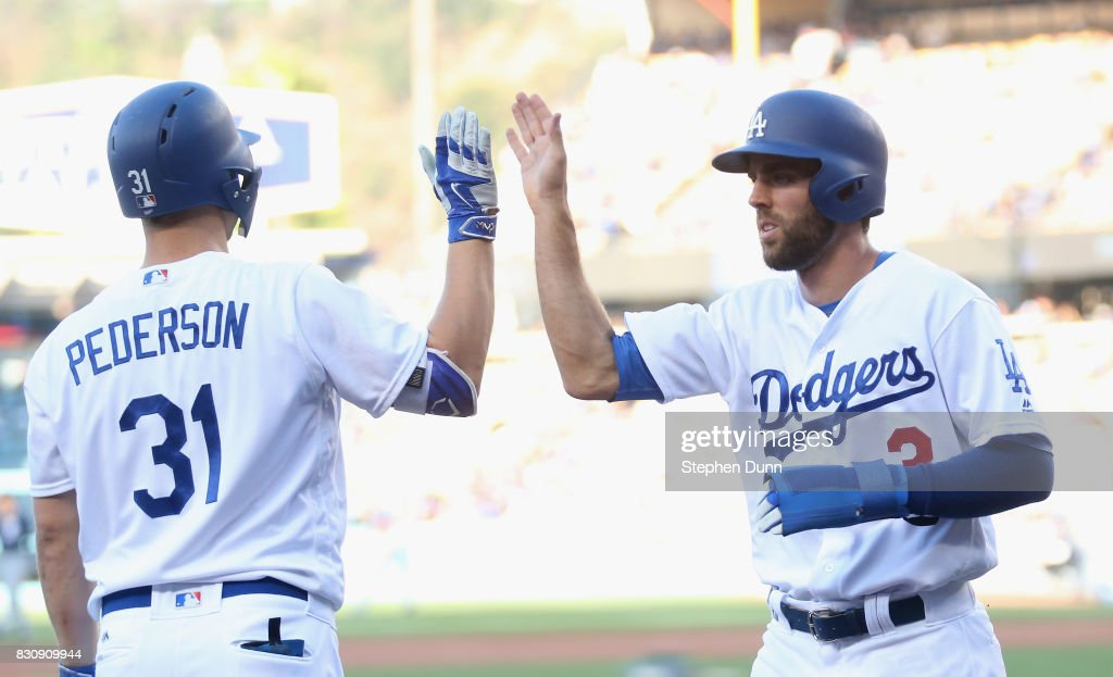 Chris Taylor #3 of the Los Angeles Dodgers is greeted Joc Pederson #31 as he returns to the dugout after scoring a run in the first inning against the San Diego Padres at Dodger Stadium on August 12, 2017 in Los Angeles, California.