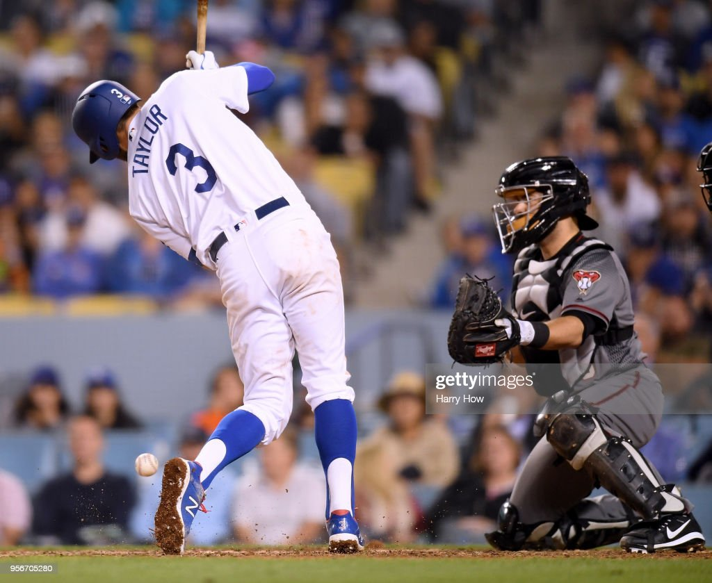 Chris Taylor #3 of the Los Angeles Dodgers is hit by a pitch in front of Alex Avila #5 of the Arizona Diamondbacks, scoring Austin Barnes #15 with the bases loaded to take a 3-1 lead during the sixth inning at Dodger Stadium on May 9, 2018 in Los Angeles, California.