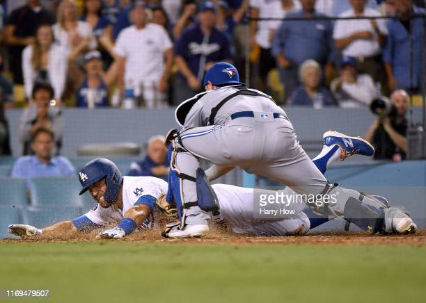 Chris Taylor of the Los Angeles Dodgers reacts as he is tagged out by Reese McGuire of the Toronto Blue Jays attempting to stretch a triple into an...