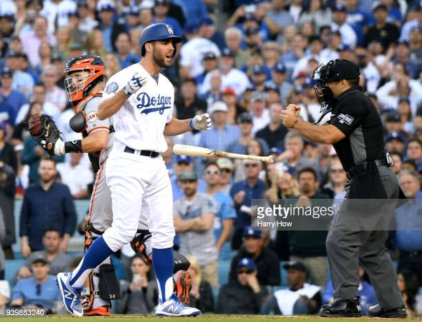Chris Taylor of the Los Angeles Dodgers reacts to his strikeout in front of Buster Posey of the San Francisco Giants during the seventh inning on the...