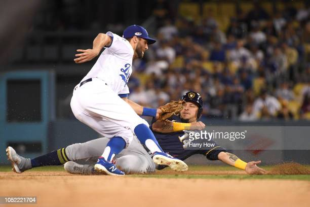 Chris Taylor of the Los Angeles Dodgers tags out Hernan Perez of the Milwaukee Brewers as he is caught attempting to steal second base during the...