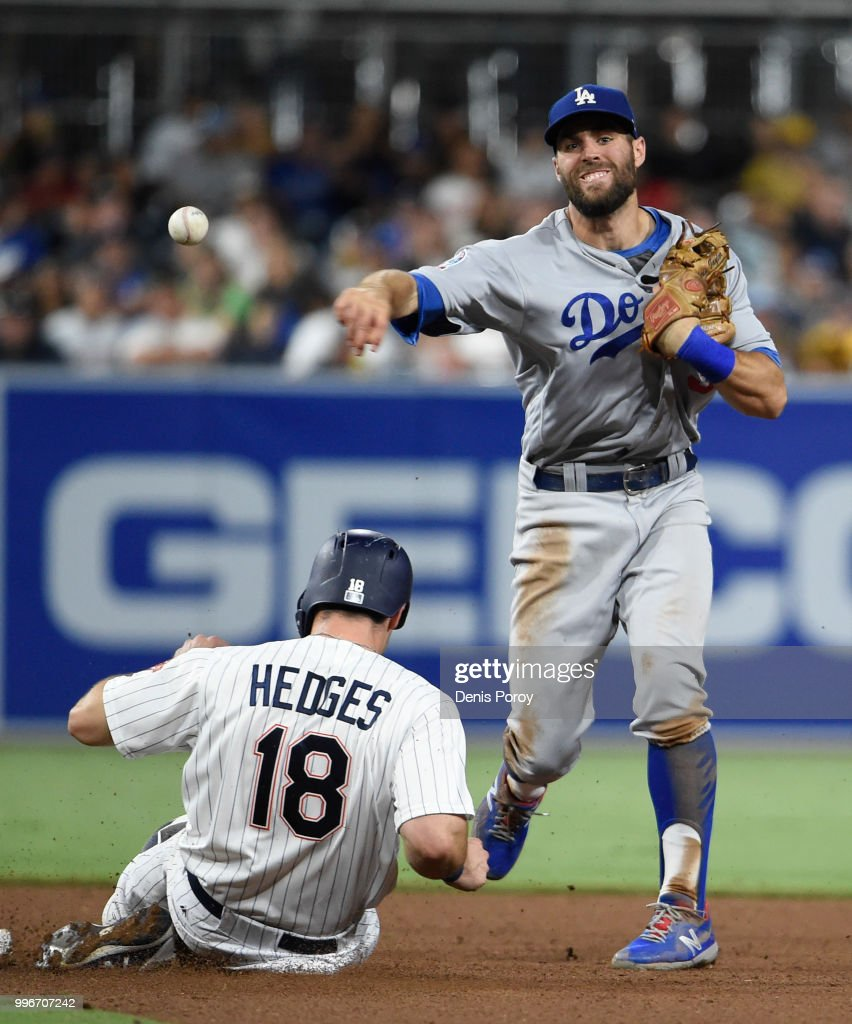 Chris Taylor #3 of the Los Angeles Dodgers throws over Austin Hedges #18 of the San Diego Padres as he turns a double play during the fifth inning of a baseball game at PETCO Park on July 11, 2018 in San Diego, California.