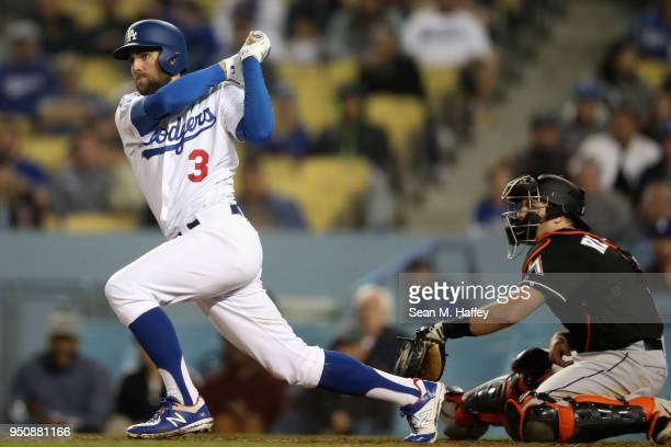 Chris Taylor of the Los Angeles Dodgers watches a hit as JT Realmuto of the Miami Marlins looks on during the fifth inning of a game at Dodger...