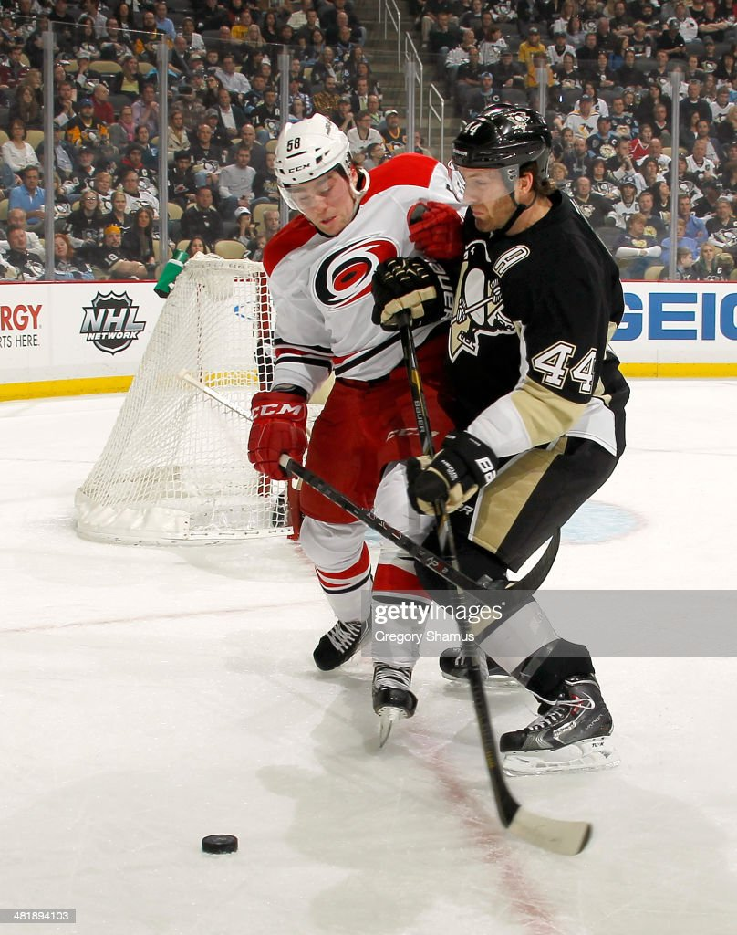 Chris Terry #58 of the Carolina Hurricanes battles for the puck against Brooks Orpik #44 of the Pittsburgh Penguins on April 1, 2014 at Consol Energy Center in Pittsburgh, Pennsylvania.