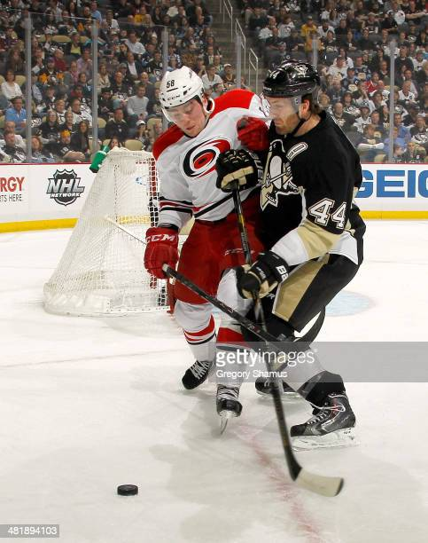 Chris Terry of the Carolina Hurricanes battles for the puck against Brooks Orpik of the Pittsburgh Penguins on April 1 2014 at Consol Energy Center...