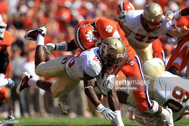 Chris Thompson of the Florida State Seminoles is tackled by Rashard Hall of the Clemson Tigers during their game at Memorial Stadium on September 24,...